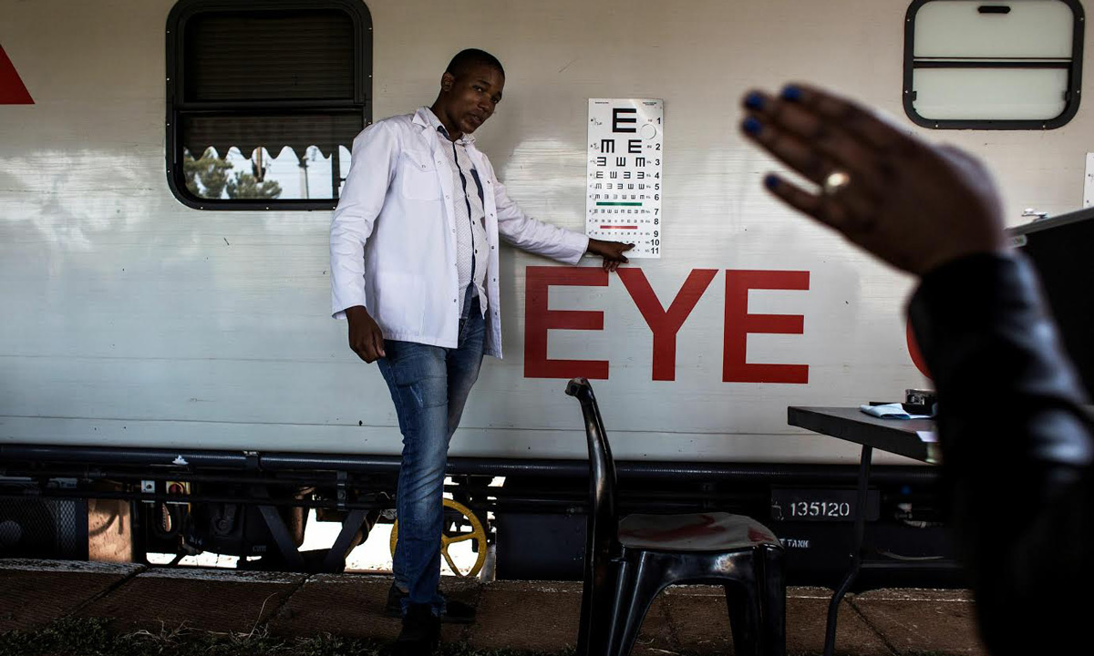 """A doctor is seen testing a patients eye sight outside the mobile health train, """"Phelophepha"""". (AFP)"""