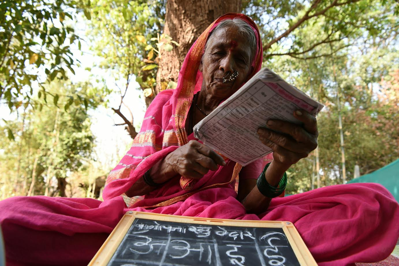 "Indian grandmother Sulochona Kedar, 68, reading from a textbook during a class at Aajibaichi Shala, or ""school for grannies"" in the local Marathi language, in Phangane village in Maharashtra state's Thane district, some 125km northeast of Mumbai. (AFP)"