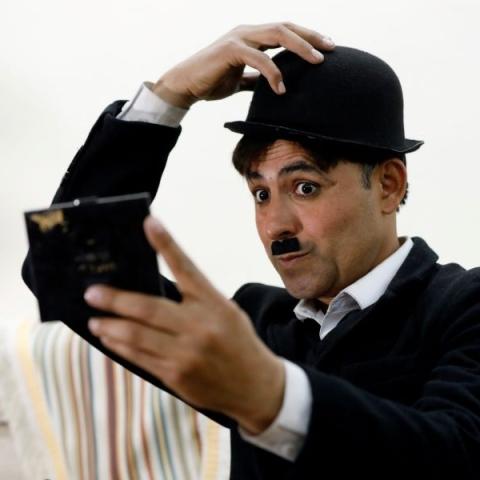 """صور: """"عثمان خان"""" .. باكستاني يتقمص شخصية """"شارلي شابلن"""" لإدخال السرور على المارين!"""